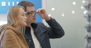 Man and woman trying on the glasses at optician's. Young couple in optical store. Man trying the glasses for visison correction while woman choosing sunglasses stock video