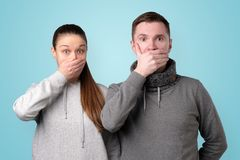 Man and woman trying to keep secret. Man and women covering their mouths with hands trying to be calm. Keep it in secret studio stock photos