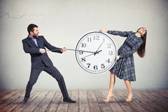 Man and woman are trying to slow down the time. Woman is intensively holding the big round clock while the men is pulling an hour-hand as if trying to slow down Stock Image