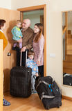 Man and woman with two children coming   home Stock Photography