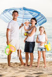 Man and woman with two kids standing together under beach umbrel Stock Image