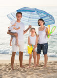 Man and woman with two kids standing together under beach umbrel Royalty Free Stock Images