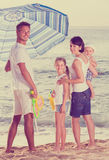 Man and woman with two kids standing together under beach umbrel Stock Photo