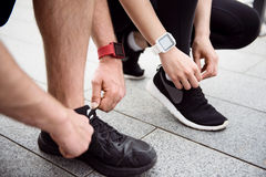 Man and woman tying their shoelaces Royalty Free Stock Photos