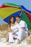 Man & Woman Under Colorful Umbrella on Beach. Man and woman romantic couple under a colorful sun umbrella or parasol on a beach Royalty Free Stock Images