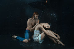 Man and a woman under water drops. Royalty Free Stock Photos