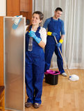 Man and woman in uniform. Professional cleaners cleaning in room at home Stock Photo
