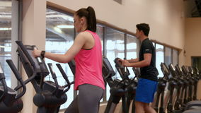 Man and woman using the cross trainers in gym stock footage