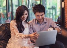 Man and woman using laptop in cafe stock image