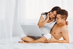Man and woman using laptop at home Stock Photos