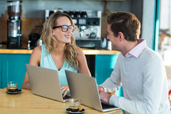 Man and woman using laptop during meeting Stock Images