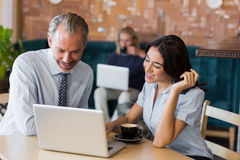 Man and woman using a laptop during meeting Royalty Free Stock Image