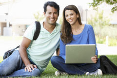 Man and woman using laptop outdoors Stock Image
