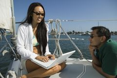 Man with woman using laptop on sailboat Royalty Free Stock Image