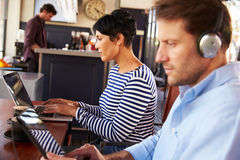 Man and woman using laptops in a restaurant Royalty Free Stock Photography