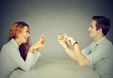 Man woman using mobile phones texting taking pictures Royalty Free Stock Photos