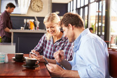 Man and woman using smart phones at coffee shop Royalty Free Stock Images