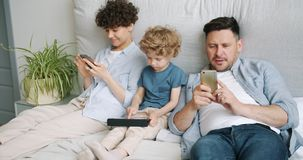 Man and woman using smartphones while kid playing game on tablet in bed at home. Man and woman are using smartphones checking social media while little kid is stock footage