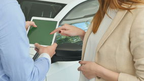 The man and woman using the tablet in the car showroom. The man is holding an electronic tablet. A woman stands by her side and presses the screen with her stock video footage