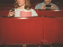 Man and woman using their phones in theater Stock Photography
