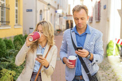 Man and woman using their smartphones Stock Images