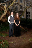 Man and woman in Victorian clothing in the park. Man and women in Victorian Clothing in the park in front of a house and trunks of trees Stock Photo