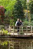 Man and woman in Victorian fashion near lake in park Stock Photos