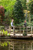 Man and woman in Victorian fashion near lake in park Royalty Free Stock Images
