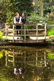 Man and woman in Victorian fashion near lake with reflections  in park Royalty Free Stock Photos