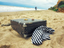 Man and woman in walk on the sand along the sea, frock valise Stock Photos