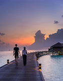 Man and woman walkiing back to their water villa i Royalty Free Stock Photography