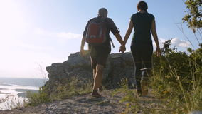 Man and woman walking along a mountain path. Tourist footwear.  stock video