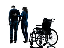 Man with woman  walking away from  wheelchair  silhouette Royalty Free Stock Photo