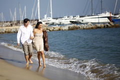 Man and woman walking on beach Stock Images