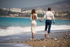 A man and a woman walking on the beach royalty free stock photos