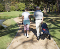 Man and woman walking on a golf course Royalty Free Stock Images
