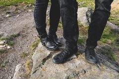Man and woman walking in the mountains, standing on a stone, legs close-up royalty free stock images