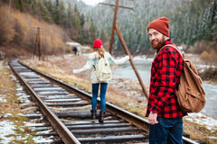 Man and woman walking on old railroad in mountains. Happy young men and women with backpacks walking on old railroad in mountains Stock Image