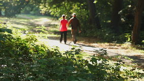 Man and woman walking outdoors on sunny day stock video