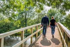 Man and woman walking over a simple wooden bridge. An unidentified man and woman in casual clothes and shoes walk over a simple wooden bridge over a narrow river stock photos