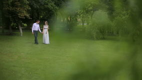 Man and woman walking in park in elegant dress. Beautiful elegant couple in love, walking in the park, romantic date. Stylish man and woman in white dress. In stock video footage