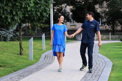 Man and woman are walking in the park. Man and women are walking in the park. They are holding their hands, smiling and looking to each other Royalty Free Stock Photos