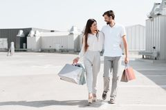 Man and woman are walking on road near parking after shopping in mall. royalty free stock photos