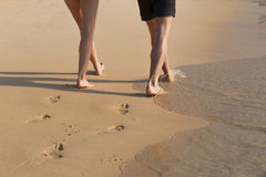 A man and a woman walking on the sand by the sea. Feet of mаn and womаn walking on the sand Stock Photography