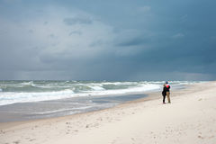 Man and a woman walking on the sea Royalty Free Stock Photo
