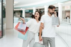 Man and woman are walking in shopping mall. Woman wants to go to store but man is busy talking on phone. stock photography