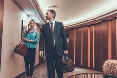 Man and woman walking with their suitcases in hotel stock photos
