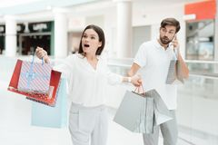 Man and woman are walking to another store in shopping mall. Man is talking on phone. stock image