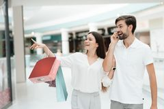 Man and woman are walking to another store in shopping mall. Man is talking on phone. stock images