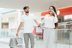 Man and woman are walking to another store in shopping mall. Woman is talking on phone. stock photo